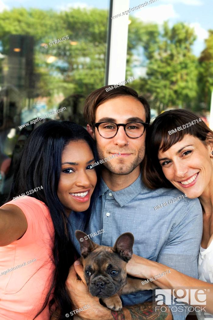 Stock Photo: Friends posing with dog for selfie.