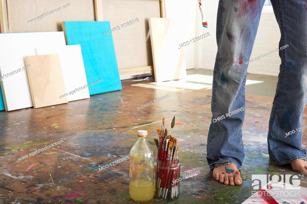 Stock Photo: Artist standing by paint brushes and paint thinner in studio low section.