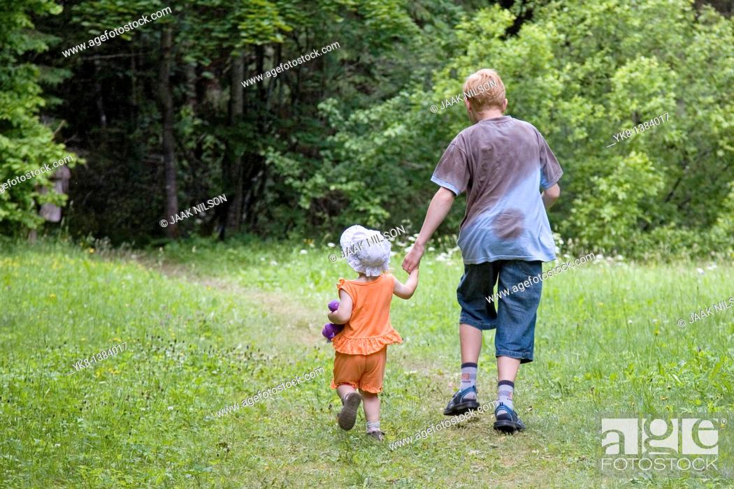 Stock Photo: Teenage Boy with Kid Girl Hand in Hand Walking Away in Forest.