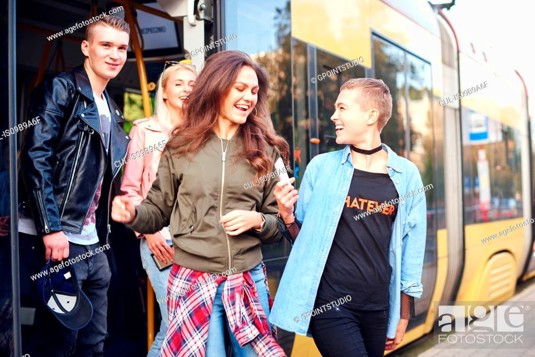 Stock Photo: Four young adult friends exiting city tram.