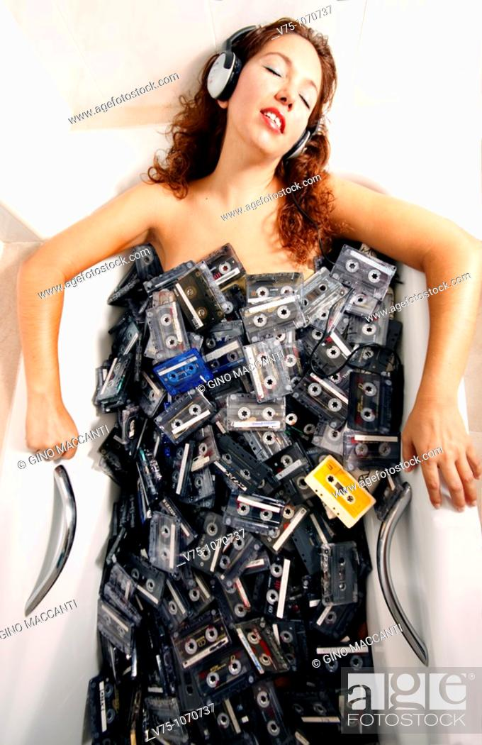 Stock Photo: Girl having a bath in a tub full of cassettes.