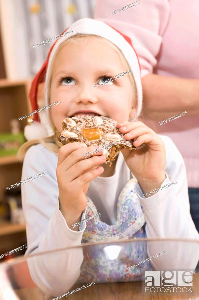 Stock Photo: Girl eating gingerbread, looking up.