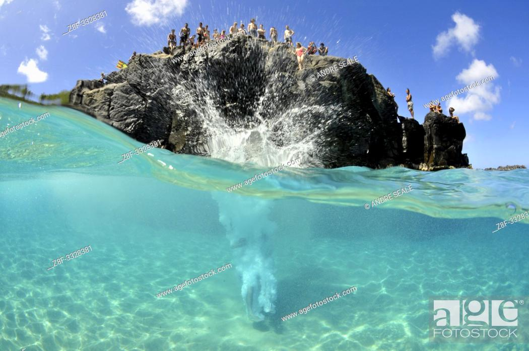 Photo de stock: Cliff diver plunges into clear waters of Waimea Bay in the summer, North Shore, Oahu, Hawaii, USA.