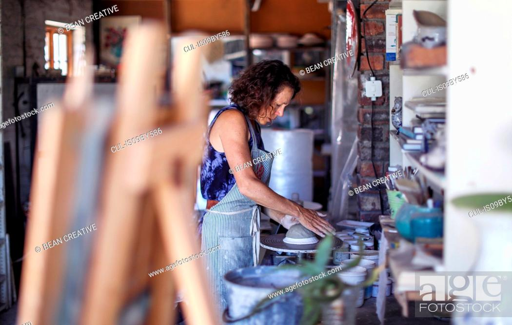 Stock Photo: Female potter shaping clay on pottery wheel in workshop.