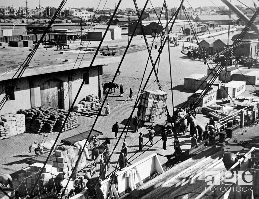 Stock Photo: Alexandria, Egypt: c. 1930 A view of the cargo and shipping industry at the docks in the Alexandria harbor.