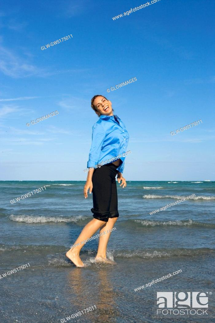 Stock Photo: Side profile of a mid adult woman standing on the beach.