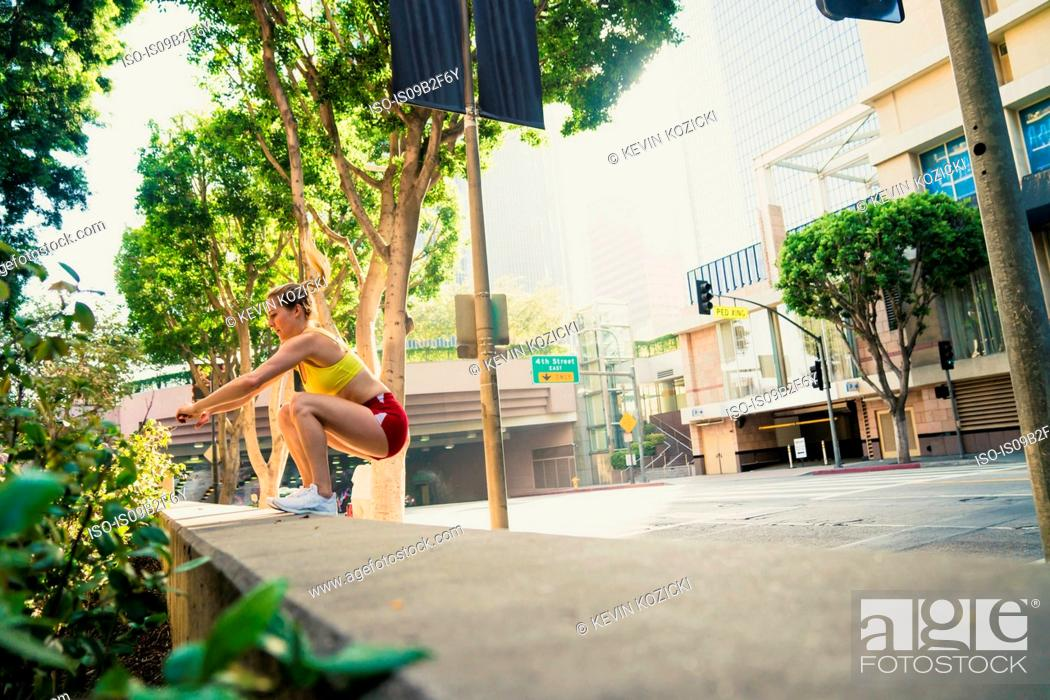 Stock Photo: Young woman exercising outdoors, jumping onto wall.
