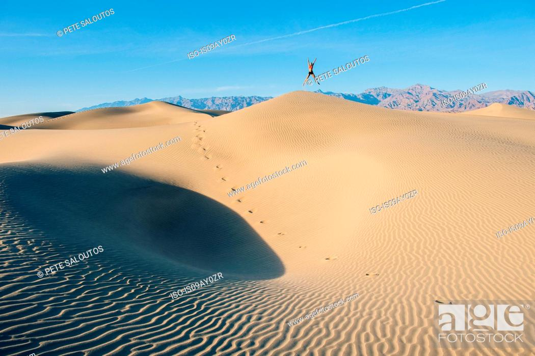 Stock Photo: Person jumping up with arms and legs outstretched on sand dune, Death Valley, California, USA.
