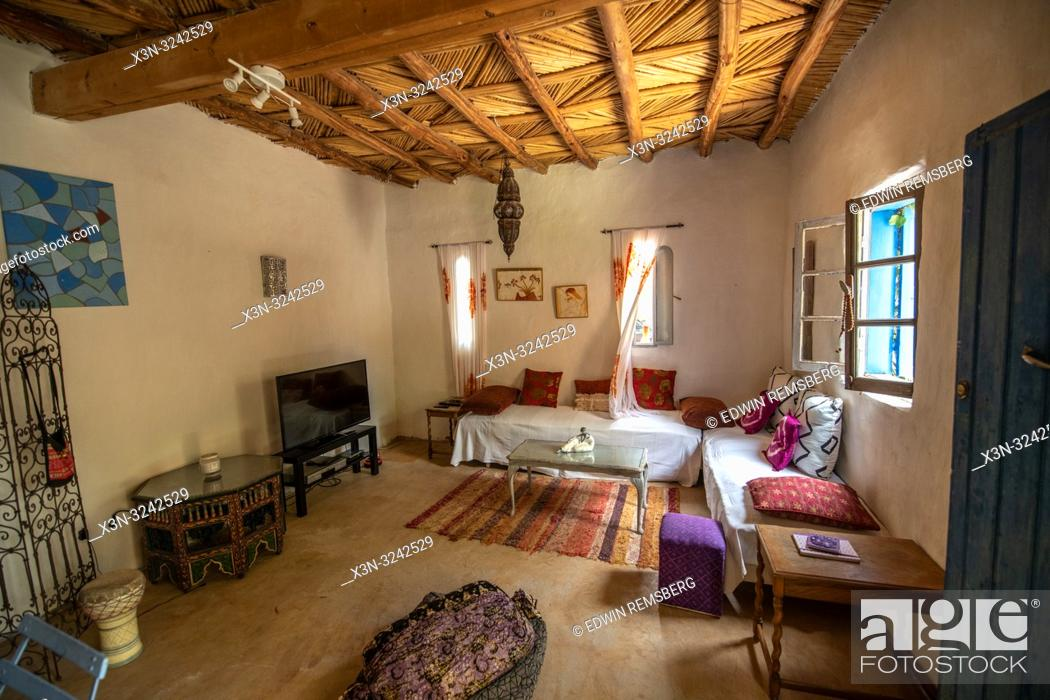 Stock Photo: Interior of living room with thatch ceiling in traditional mud-brick built home in Tighmert Oasis, Morocco.