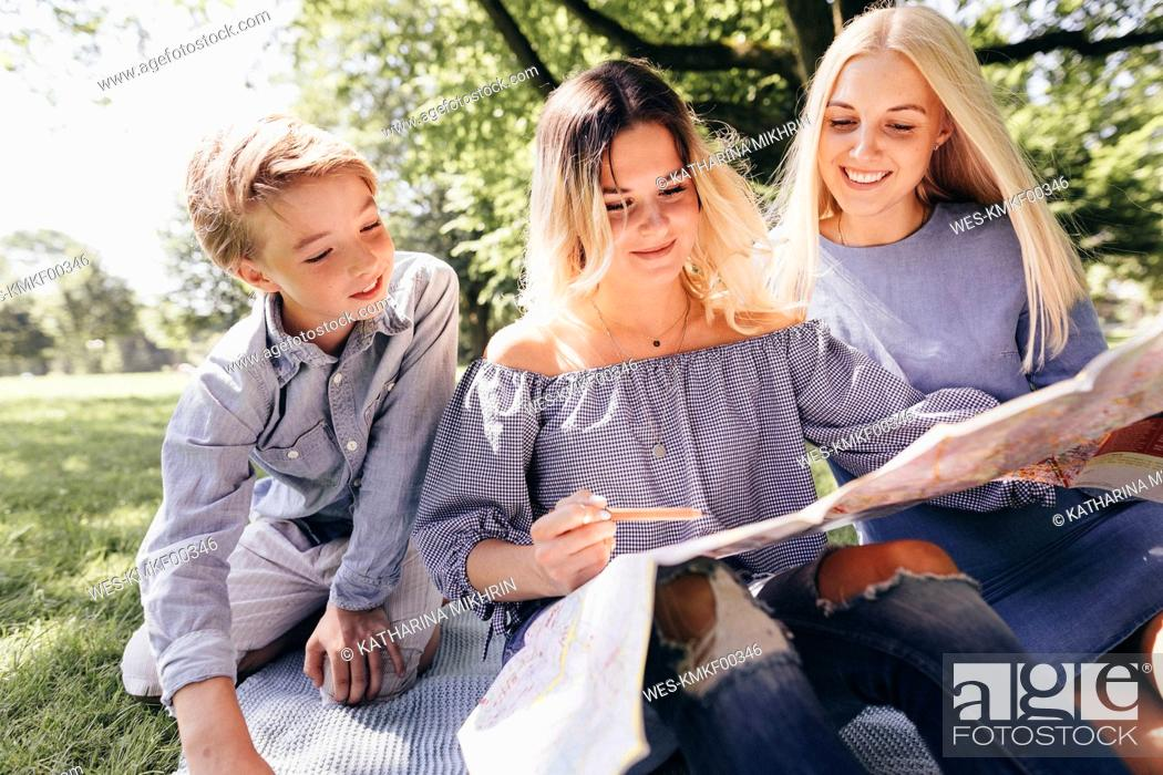 Photo de stock: Two young women and a boy looking at map in a park.