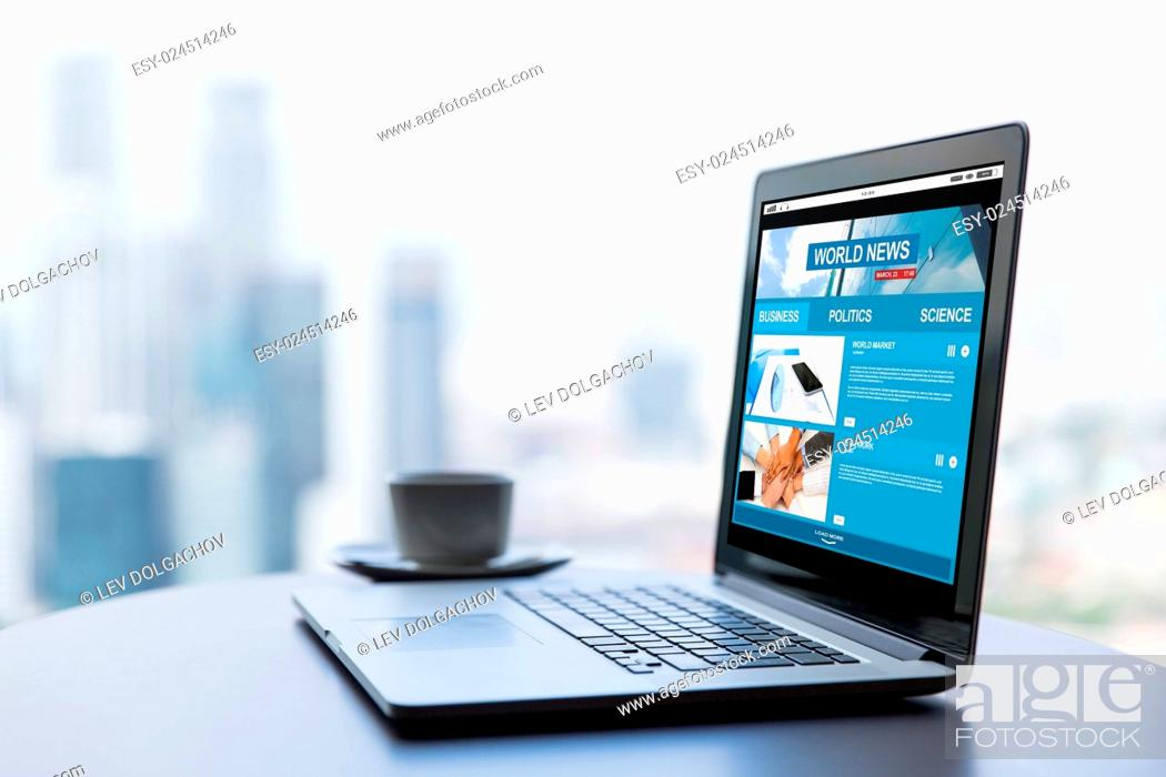 Stock Photo: technology, business, mass media and modern life concept- close up of open laptop computer with news web site on screen and coffee cup on table at office or.