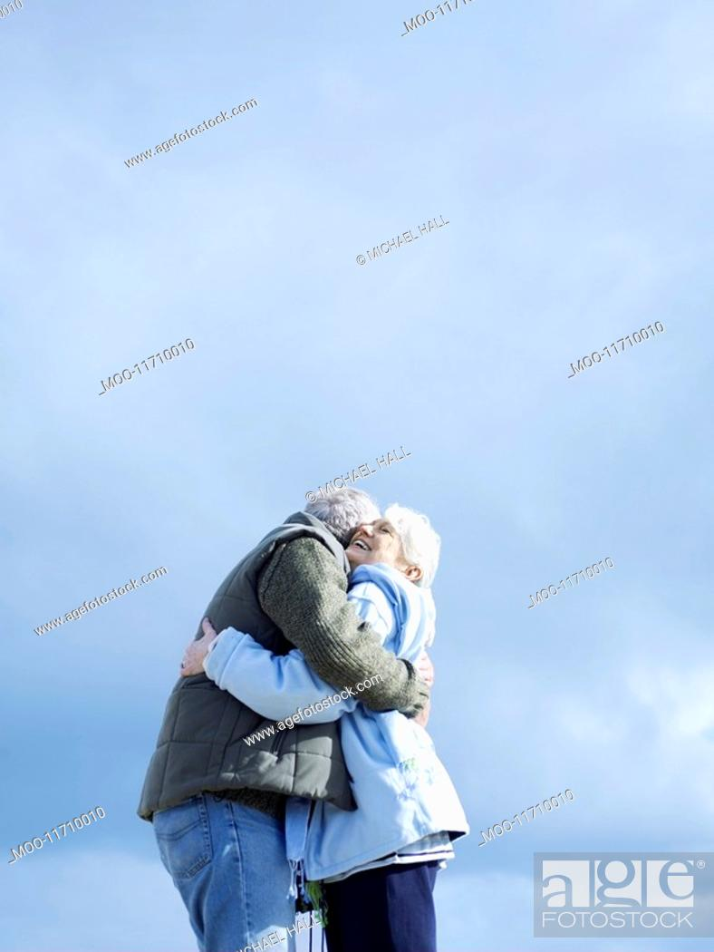 Stock Photo: Senior couple embracing outdoors low angle view.
