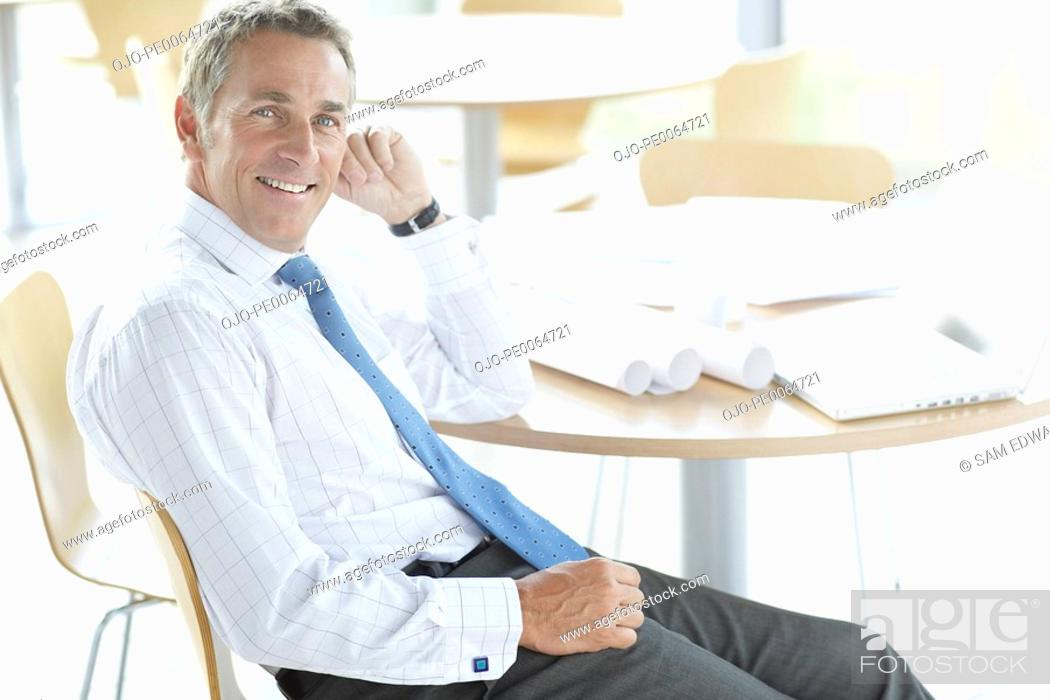 Stock Photo: Businessman sitting at desk with blueprints.