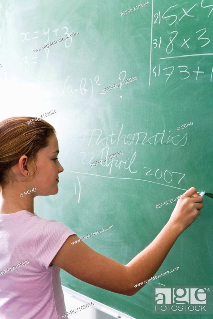 Stock Photo: School girl 10-13 writing on blackboard in classroom.