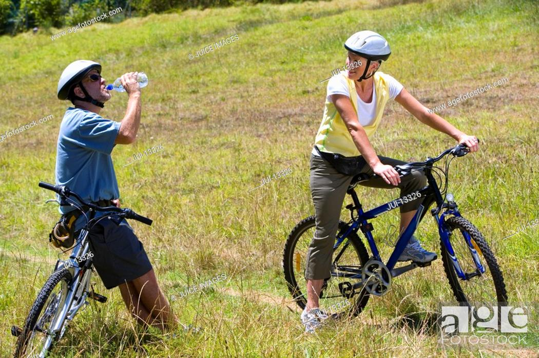 Stock Photo: Couple with bicycles in countryside, man drinking from water bottle.