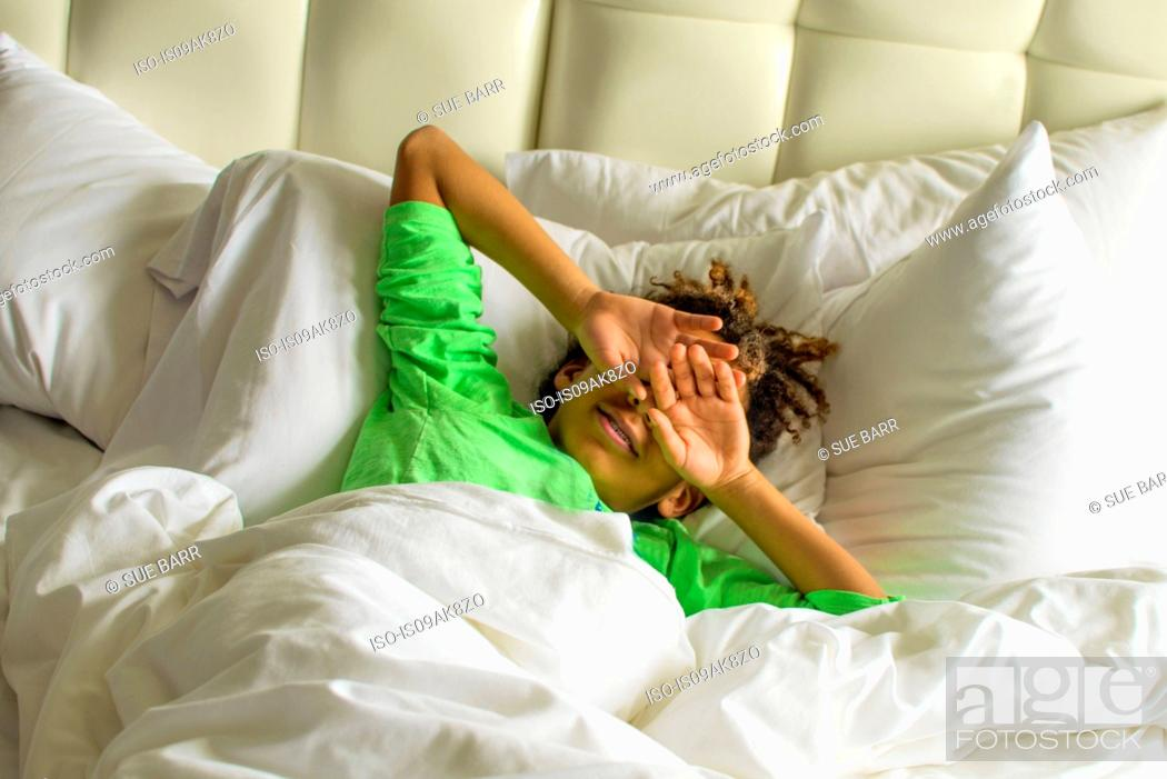 Stock Photo: Sleepy boy lying in bed shielding face with hands.