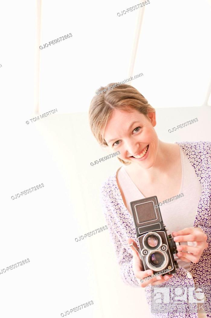 Stock Photo: Smiling woman holding retro camera.