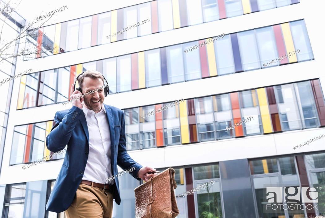 Stock Photo: Happy businessman listening to music with headphones.