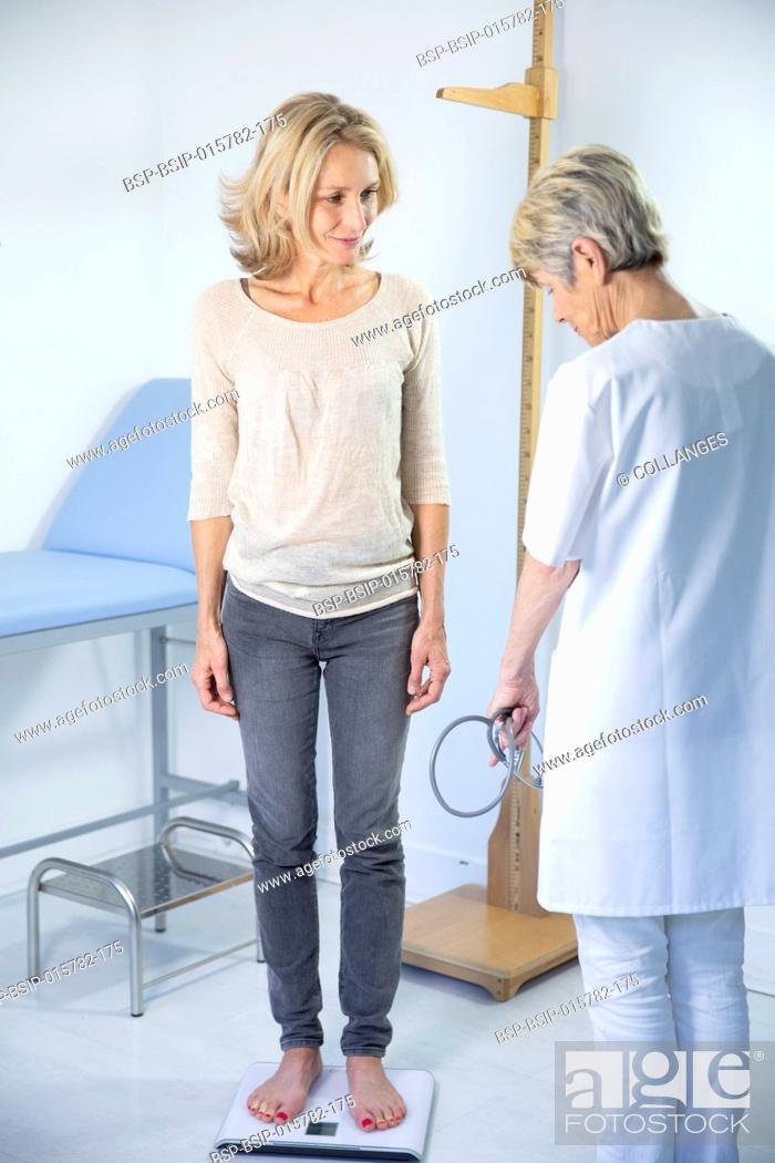 Stock Photo: Woman being weighed at the doctor's.