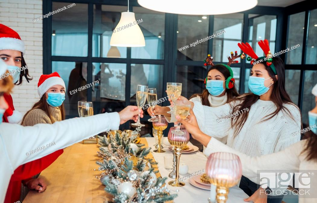 Photo de stock: Multi-ethnic young people celebrating New year eve clinking glasses toasting, multiracial friends having fun at party celebration.