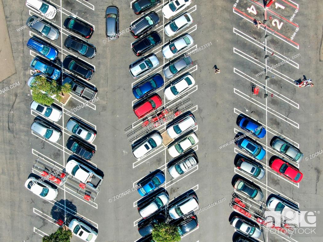 Stock Photo: Aerial top view of parking lot at shopping mall with varieties of colored vehicles. People walking to their car and trying to park.