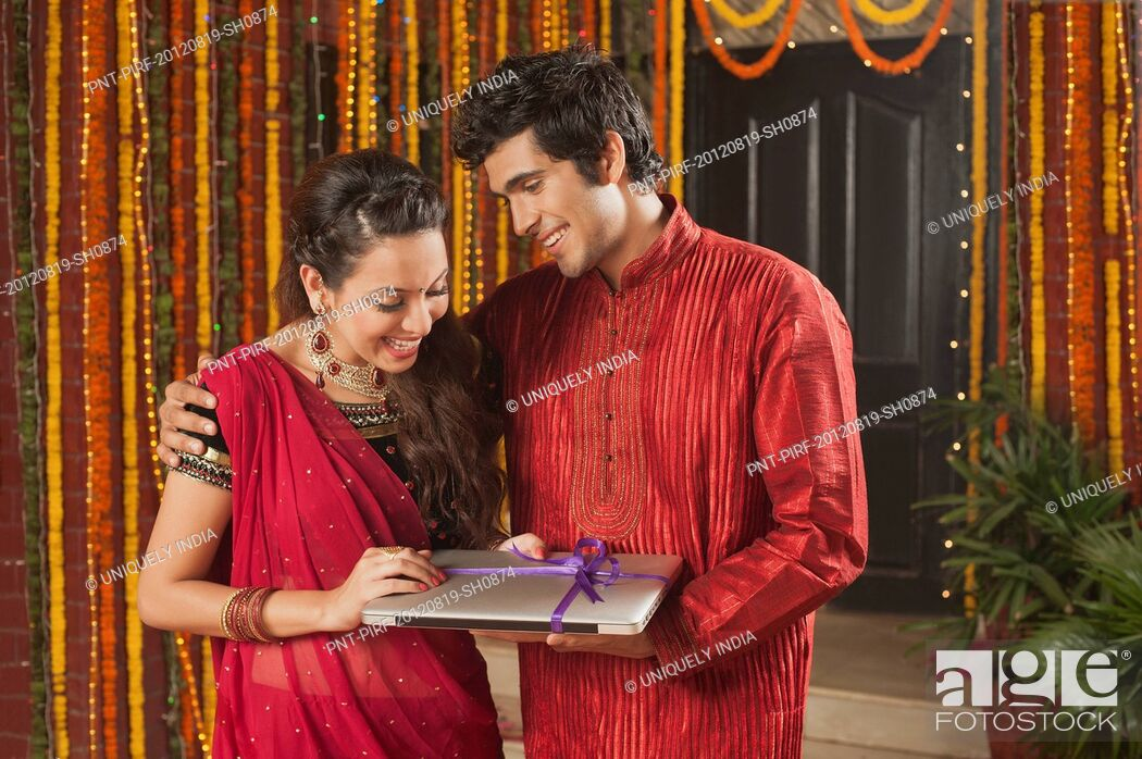 Stock Photo: Man giving a laptop to his girlfriend on Diwali.