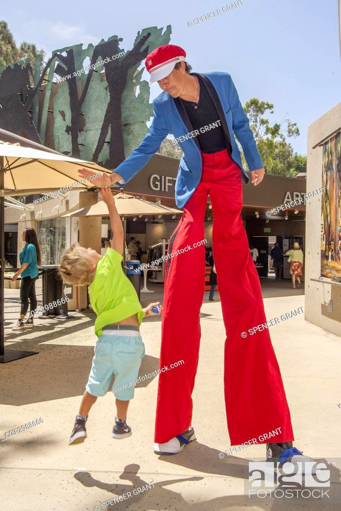 Stock Photo: A costumed stilt walker shares a high five with an exuberant boy toddler at an art festival in Laguna Beach, CA.