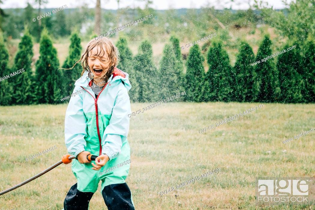 Stock Photo: girl laughing whilst playing with water in the yard at home.
