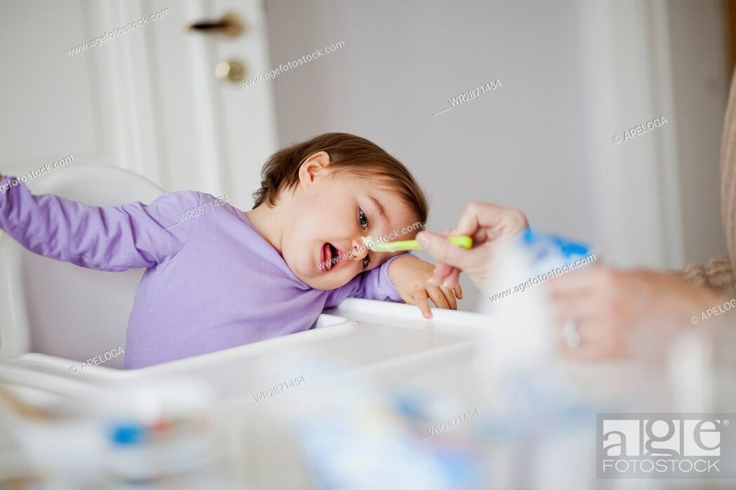 Stock Photo: Mother feeding daughter with spoon at home.