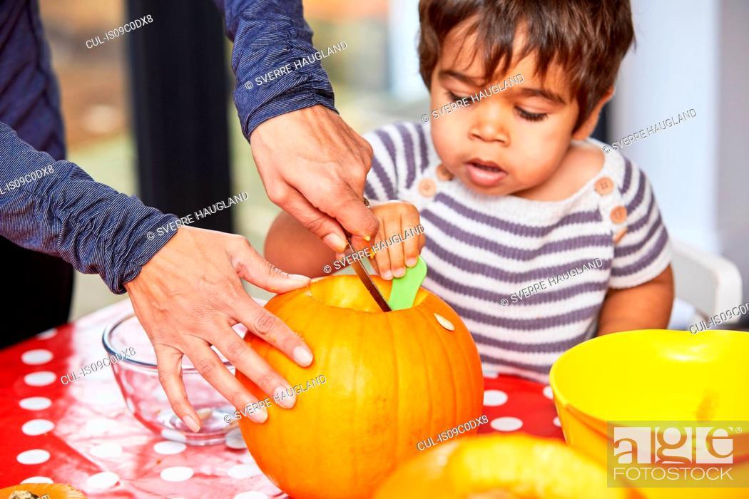 Stock Photo: Boy helping mother gut pumpkin in kitchen.