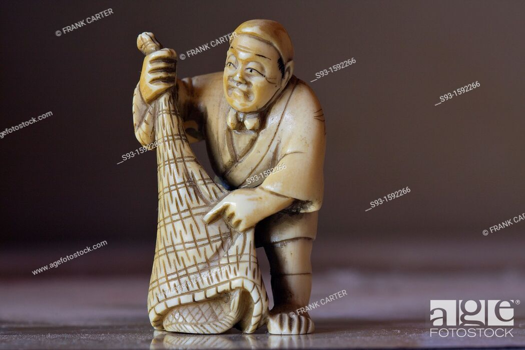 Stock Photo: A close up of a small ivory figure of a fisherman and his net.