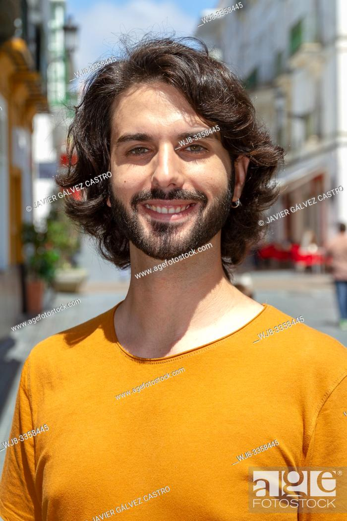 Stock Photo: portraits of a young man on street, looking at camera while smile with a t-shirt orange.