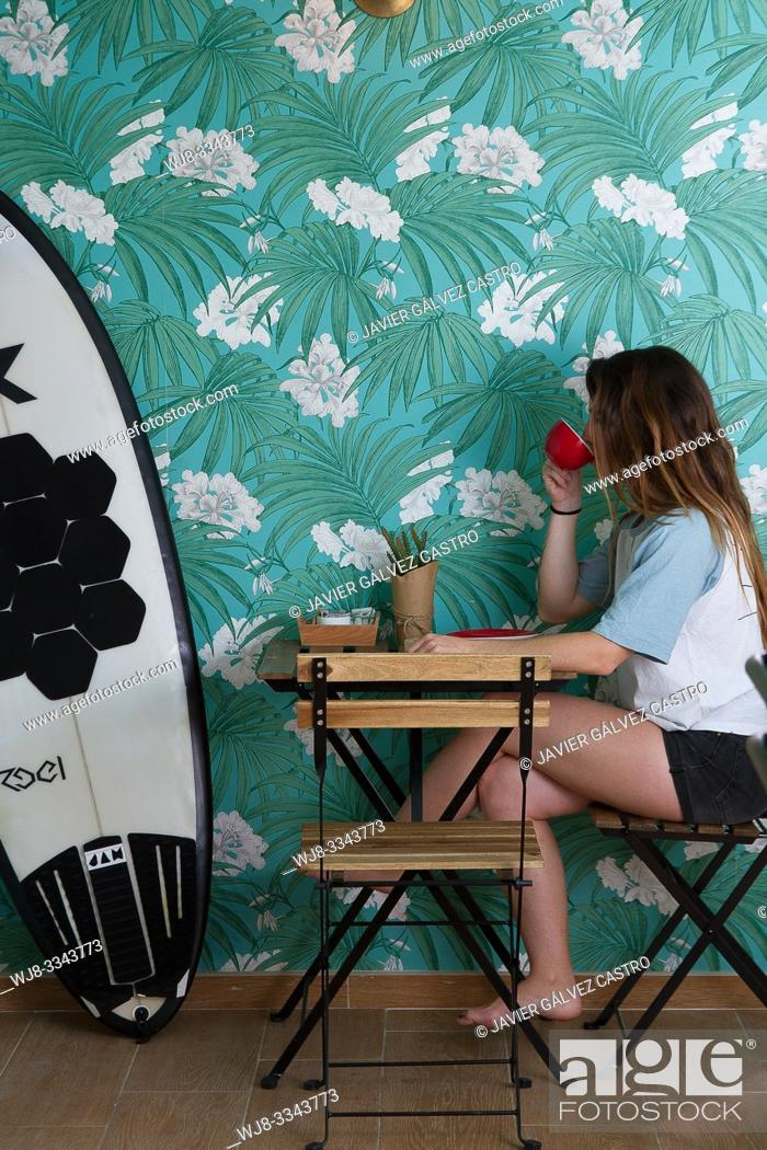 Stock Photo: Young woman drinking coffee, in a cafe, next to your surfboard.