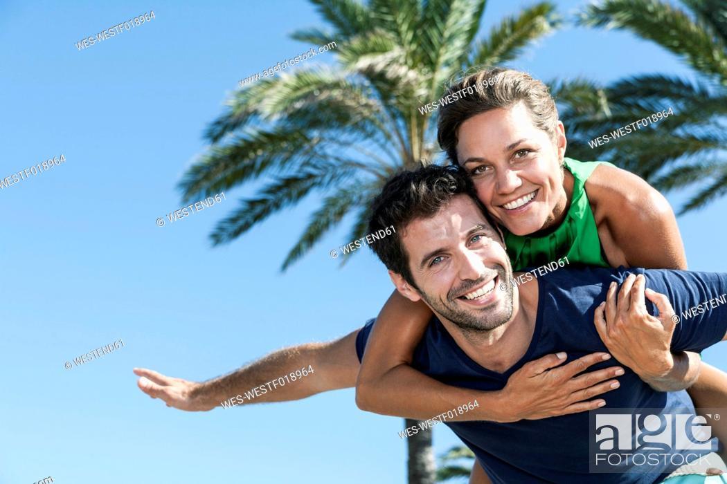 Stock Photo: Spain, Mid adult man giving piggy back ride to woman, smiling.