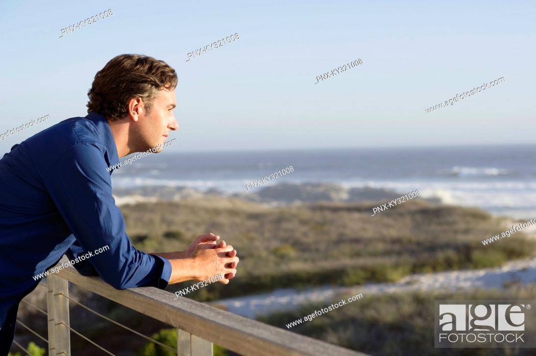 Stock Photo: Mid adult man leaning on a railing of a balcony.