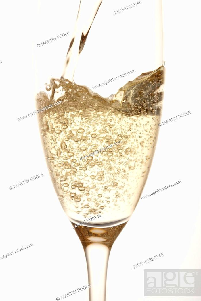 Stock Photo: Champagne being poured into glass close up in studio.
