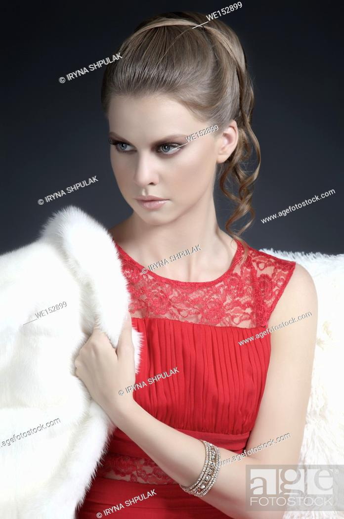 Stock Photo: Young woman in evening dress with fur coat.
