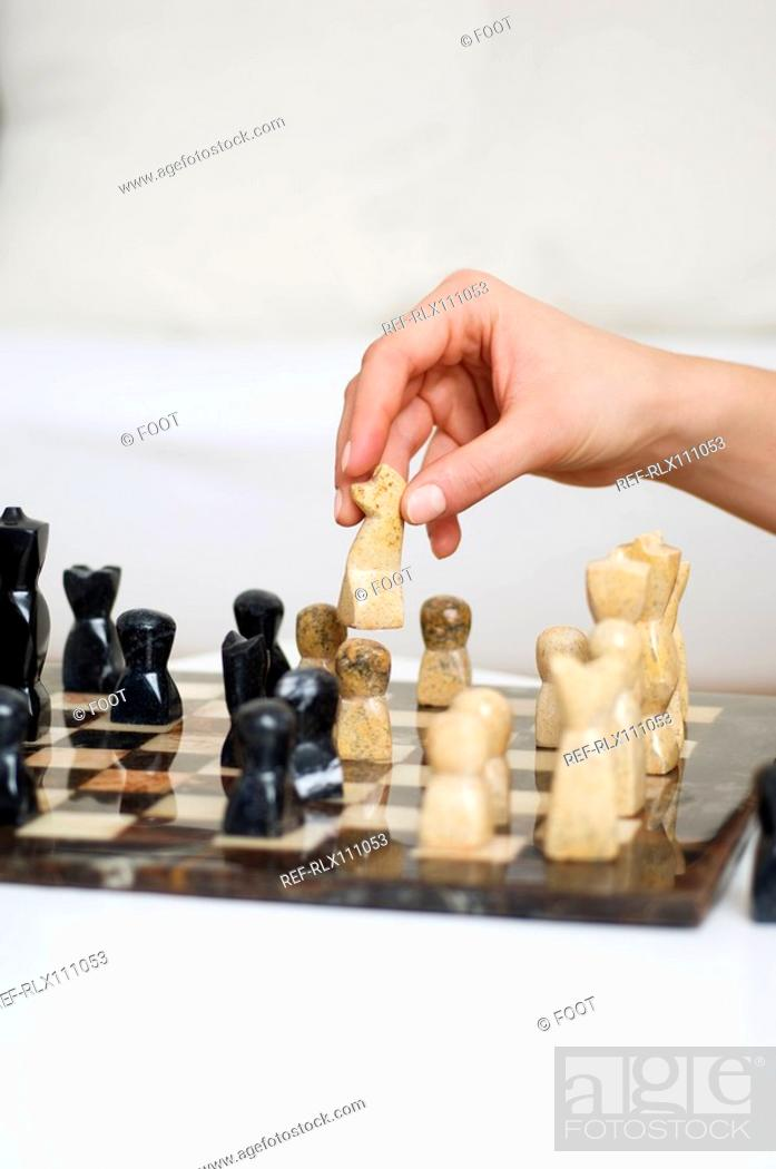 Stock Photo: Close up of person playing chess.