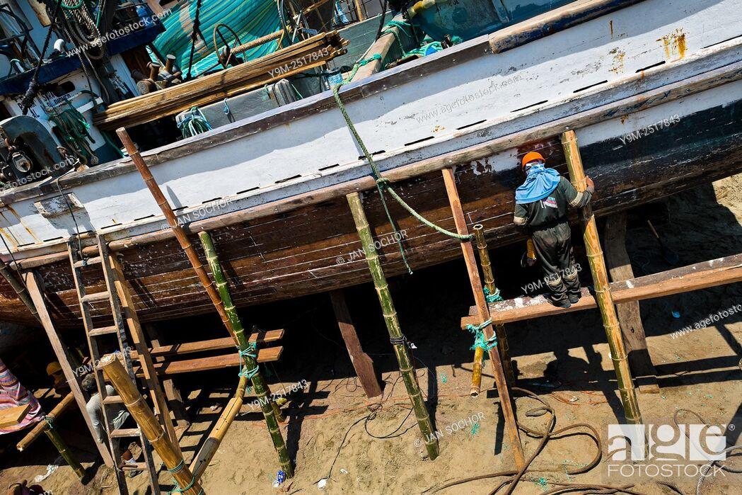 Stock Photo: An Ecuadorian shipbuilding worker repairs the shell of a traditional wooden fishing vessel in an artisanal shipyard on the beach in Manta, Ecuador.