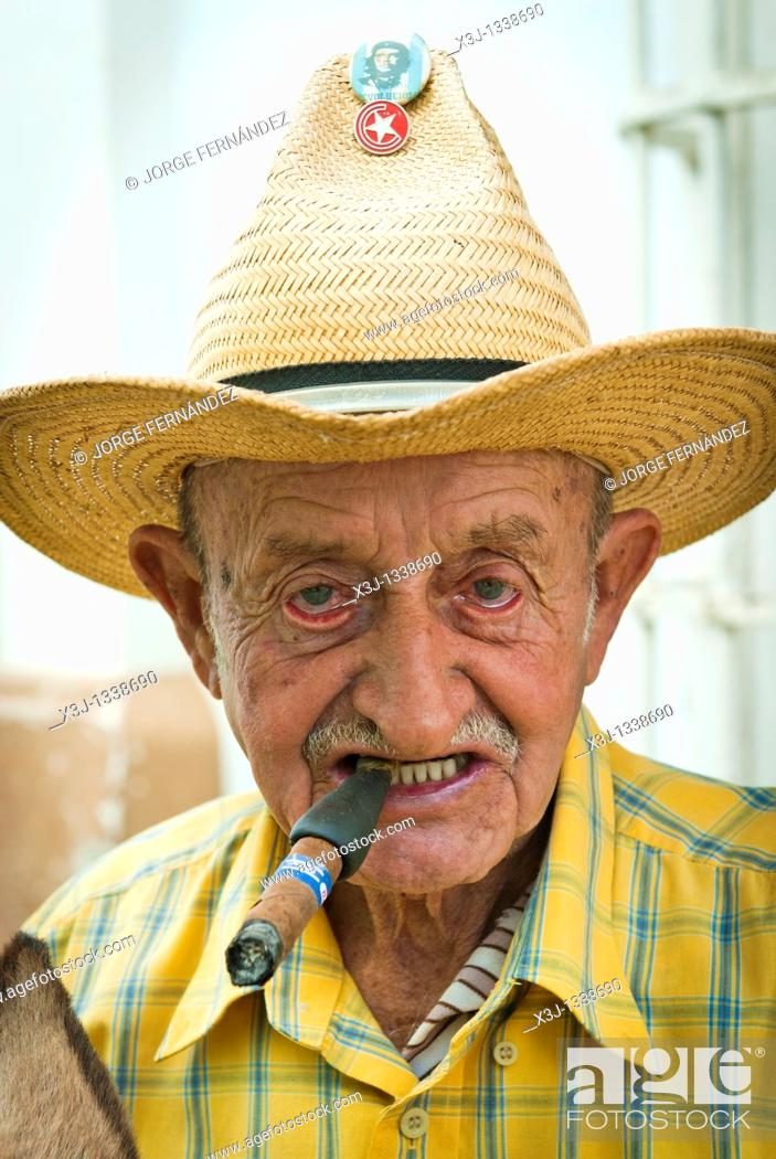 Stock Photo: Old man with a cigar and a straw hat with political badges, Trinidad, Sancti Spiritus, Cuba, Caribbean.