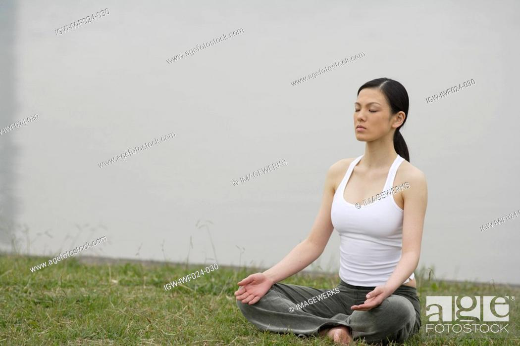 Stock Photo: Front view of a woman in lotus position.
