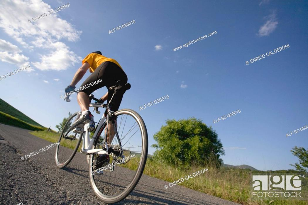 Stock Photo: Rear view of a man riding bike.
