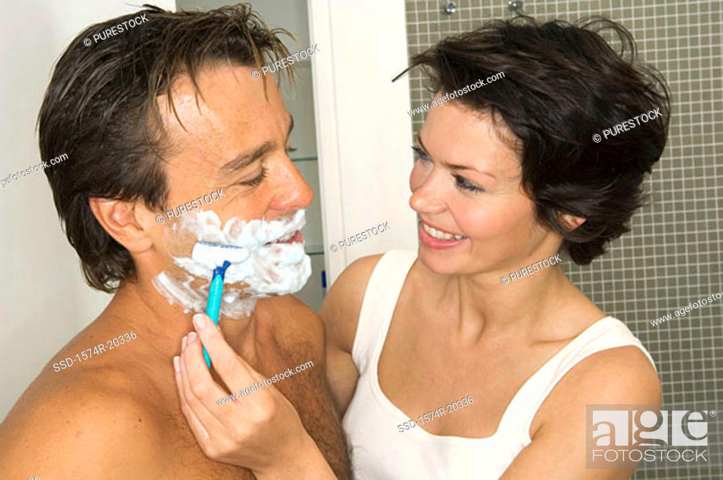 Stock Photo: Close-up of a young woman shaving the beard of a young man.
