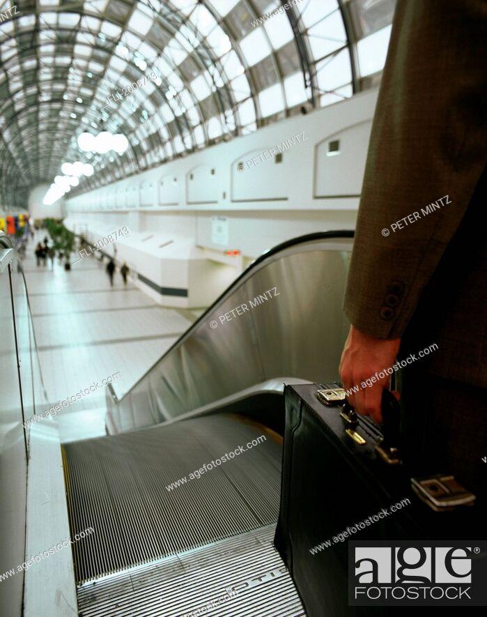 Imagen: Businessman Descending Escalator.