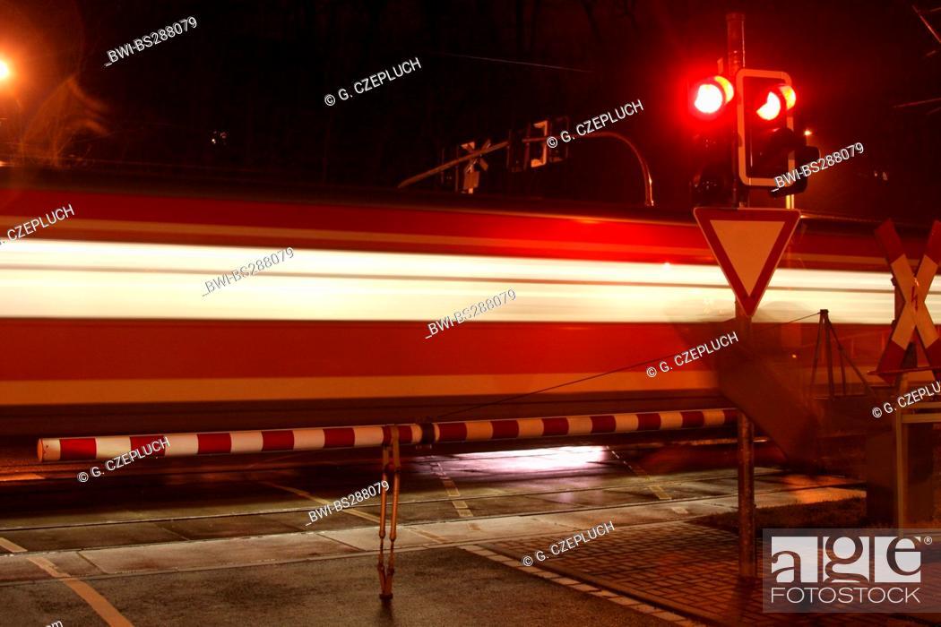 train passing a railroad crossing at night, Germany, North