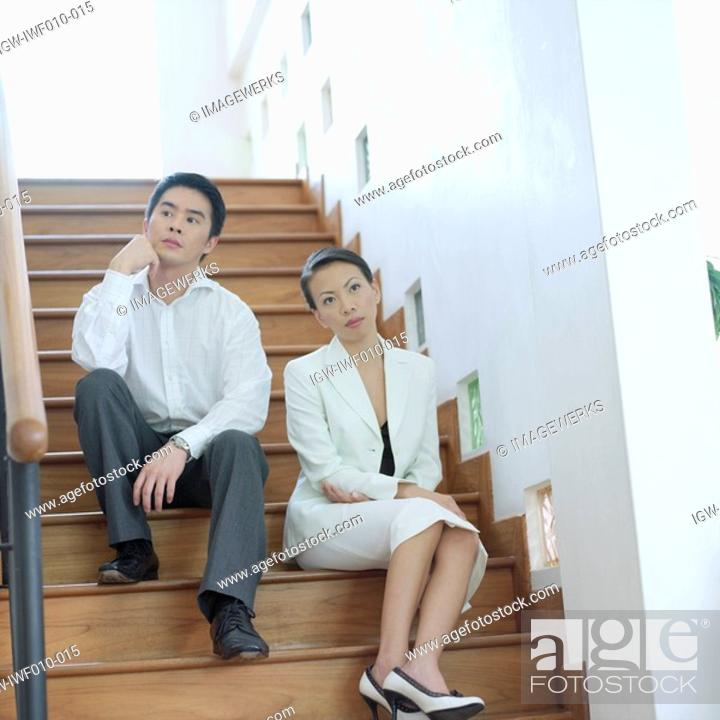 Stock Photo: Low angle view of a businesswoman and a businessman sitting on a staircase.