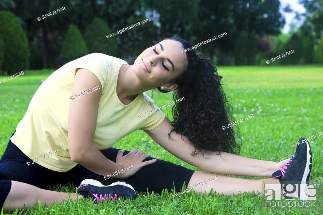 Stock Photo: Portrait of beautiful black-haired sportswoman stretching on grass with eyes closed.
