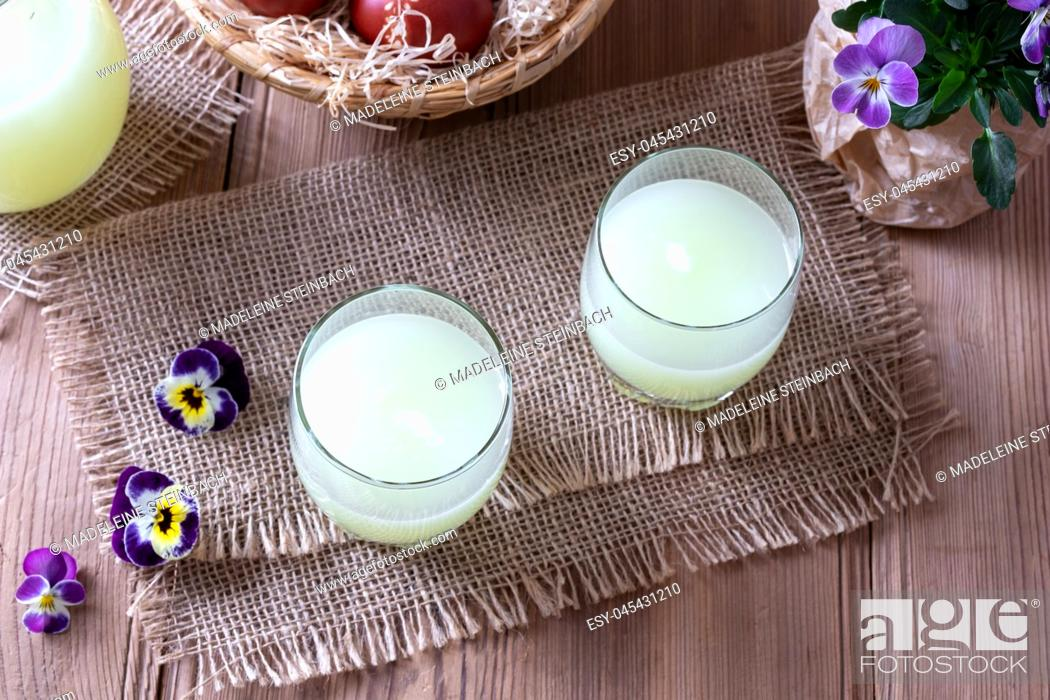 Stock Photo: Two glasses of fresh whey and pansy flowers on a table.