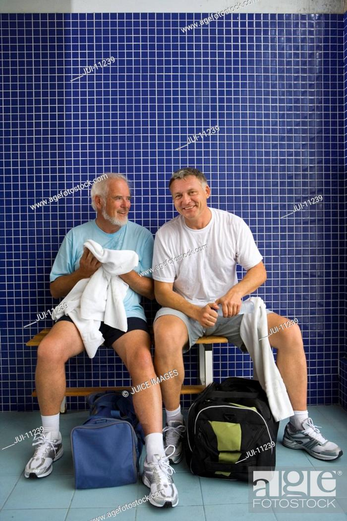 Stock Photo: Two men in gym changing rooms, one with towel, one with water bottle, portrait.