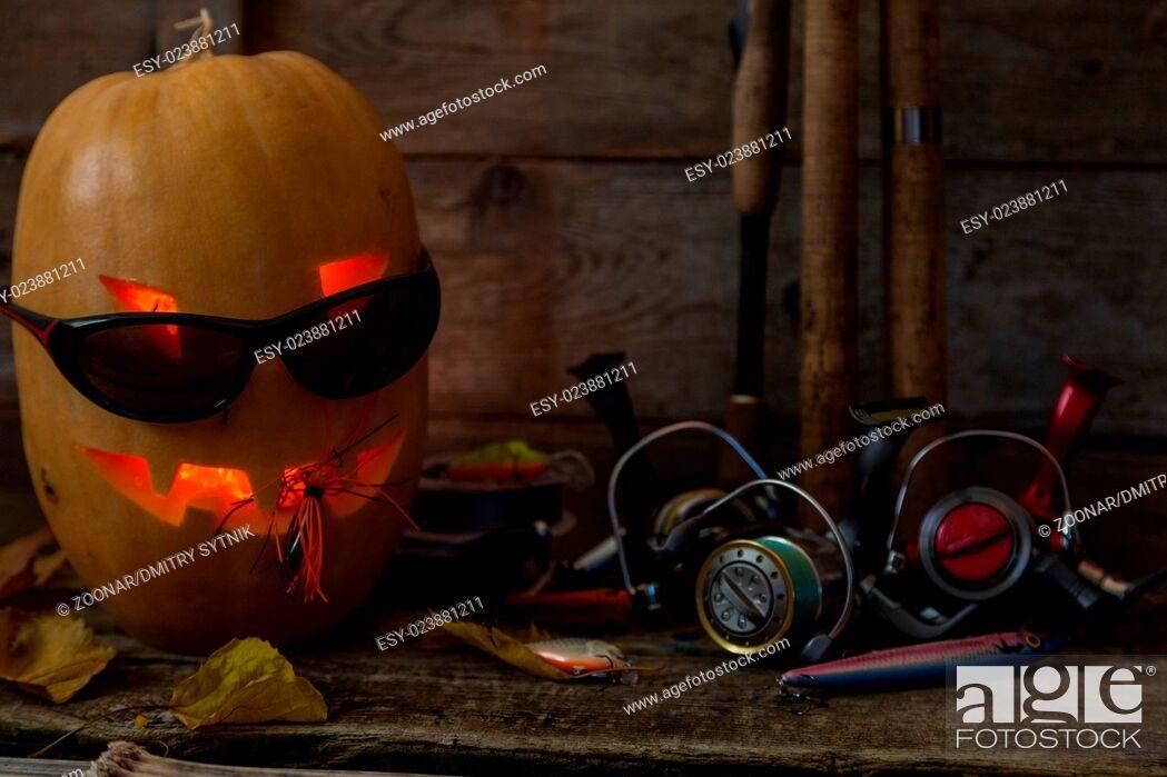 Stock Photo: halloween pumpkin head with fishing tackles.